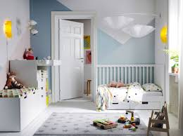 A children's bedroom furnished with a white cot with two drawers, a  changing table and