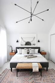 a modern black chandelier and small black sconces for a stylish modern bedroom