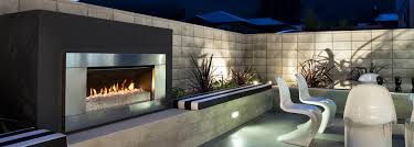 escea ef5000 gas fireplace in landscaped outdoor area with dining set at night
