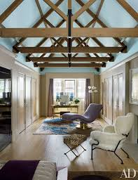 Wood beams add a rustic accent to blue ceilings in a London home designed  by Rafael
