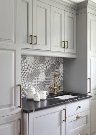 gray kitchen pantry cabinets accented with brushed brass hardware flanks gray raised panel cabinets topped with a honed black marble countertop fitted with