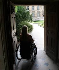 looking out door. Woman In Wheelchair Sits Dark Room Looking Out Door To Outside Courtyard A