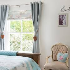 printed roman blinds layered with plain curtains are an elegant way to dress a bedroom window go for a bold pattern that coordinates with your room scheme