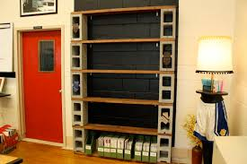 DIY Tall Book Shelves Made From Ten Concrete Blocks Plus Wooden Planks At  Black Brick Wall On Brown Laminated Flooring