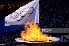 flame lighting olympics. the olympic flame burns brightly as flag waves behind it during opening ceremony lighting olympics i