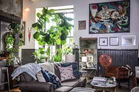 the living room where a large industrial style window facilitates plenty of sunlight