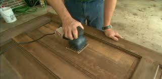 using an oscillating sander to sand the old finish off an entry door