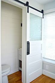 small powder room with a white painted barn door with frosted glass window
