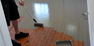 Using a roller to paint our wood floor.