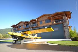 hangar home designs. a husky backcountry plane sits outside one of the beautiful hangar homes at silverwing sandpoint airpark community. schweiss bifold doors have home designs