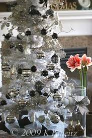 White flocked Christmas tree with black and silver ornaments