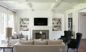 chic living room with bookshelves and cabinets filling alcoves on either side of fireplace