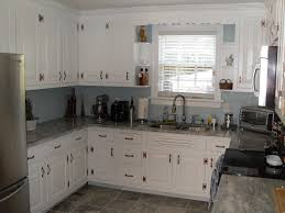 grey granite countertops connected by white wooden kitchen cabinet
