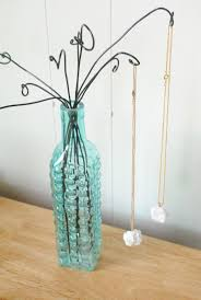 Awesome jewelry display made with wire hangers and a vintage bottle.