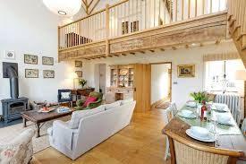 farm living room bright and spacious living area with wood burner and view of upstairs mezzanine farm living room