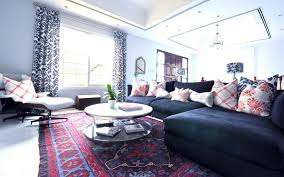 fancy red and blue motif oriental rug combine with coffee table and modern black sofa faced white lounge sofa