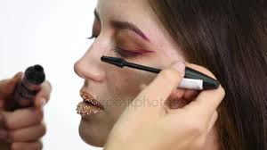 professional eye makeup mascara application model looking straight at camera work in beauty fashion industry