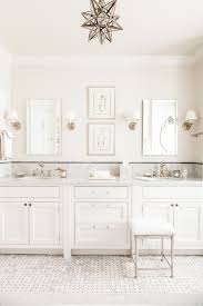 white bathroom with gray marble countertops and a glass moravian star pendant