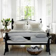white bedroom with dark furniture. mixing white with carved wood and rattan furniture creates a fresh new englandstyle bedroom dark k