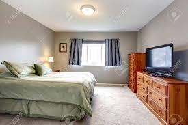 Große Graue Schlafzimmer Mit Kommode Fernseher Und Blaue Vorhänge