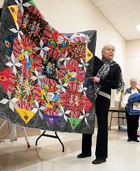 Marble Falls Quilt Club piecing together Stars of Texas Quilt Show & Peggy Wilson of the Marble Falls Quilt Club tells other members about one  of her quilts Adamdwight.com