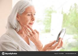 Beautiful elderly woman holding mirror and applying face cream at