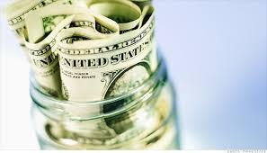 A glass jar with dollar bills in it.