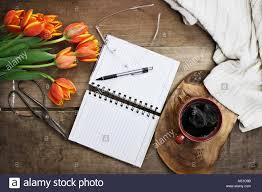 overhead shot a bouquet of an open book or garden planner gles coffee sissors and flowers over a wood table top ready to plan an agenda flat la