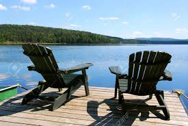 lake dock chairs. two adirondack wooden chairs on dock facing a blue lake with clouds reflections stock photo -