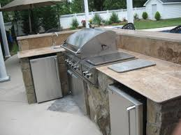 kitchen l shaped covered outdoor kitchen stainless steel bbq grill natural stone fireplace mantel brown