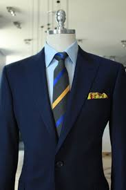Navy jacket, light blue shirt, dark grey tie with blue & yellow stripes
