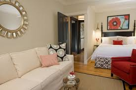trendy master bedroom with beige walls and um tone hardwood floors white sofa multi colored pillow