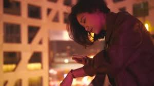 pretty young asian woman using mobile phone at night outdoor with