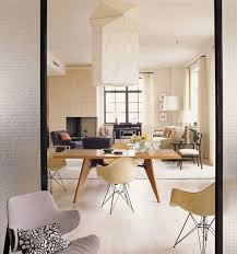 pale yellow dining room. dining room features giant noguchi akari l2 ceiling lamp also wooden table plus pale yellow eames dar armchairs besides beig armchair and light d