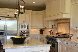 A soft stone tile backsplash with a bolder centerpiece behind the stove  top. The light