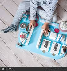 cute toddler baby playing with busy board at home busy board for for children children s educational toys wooden game board diy busyboard photo by