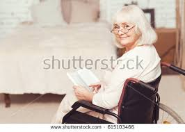 charming retired lady reading book in wheelchair at home 615103466