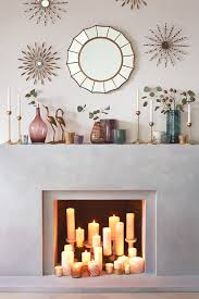 Create a modern look by layering different sized candles within your  fireplace. Pretty mirror too