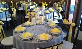 silver and yellow wedding silver table cloths and chargers with yellow sashes and napkins