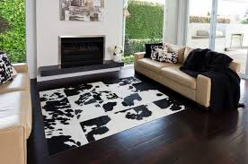 large contemporary open concept living room in sydney with white walls dark hardwood floors and fascinating patchwork cowhide rug