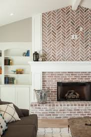 fireplace with herringbone pattern brick work and built in shelving by rafterhouse