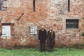 portrait of couple in front of old brick wall farm building