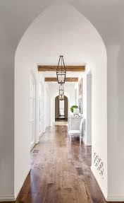 long foyer with rustic wood ceiling beams and gothic doorway
