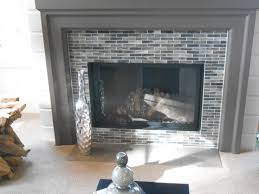 modern dark grey light white black and pale green small tile glass mosaic fireplace surround modern black metal frame and see through glass wood fireplace