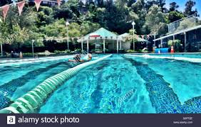 woman kicking with kickboard in outdoor olympic size 25 meter swimming pool san francisco bay
