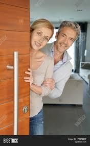 opening front door. Couple Opening House Front Door To Welcome People In