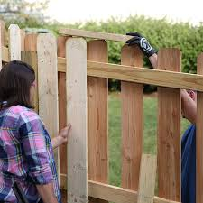 use a short board to help maintain the correct height for inside fence pickets