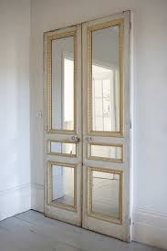 pair of old doors with mirror inserts against a plain wall or on closet love this idea for our bedroom