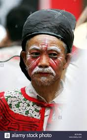 elderly chinese man in heavy makeup and costume paring in parade held during temple fair