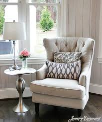 create a cozy sitting area in the corner of your living room by using an upholstered chair and a small side table featuring bright flowers